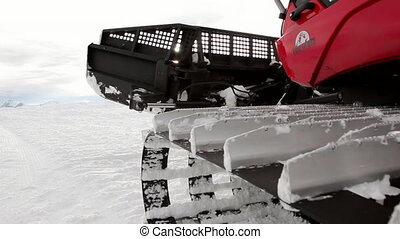 Snowcat Working on the Piste - A snowcat is moving on the...