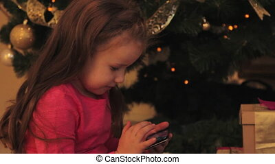Little Girl with Smartphone by the Christmas Tree