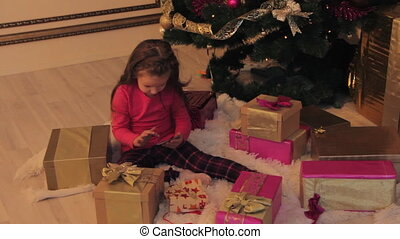 Girl Playing in Smartphone by Christmas Tree - Little girl...