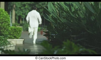 a man running in the garden - a Chinese man running in...