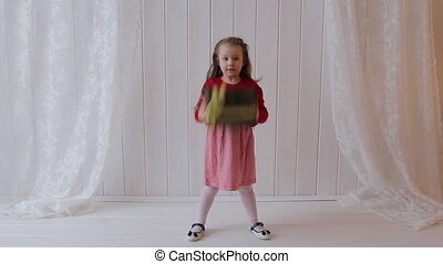 Girl Jumping with Gift Box - Little girl is holding gift box...