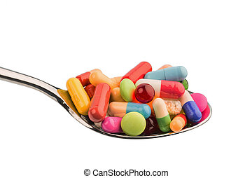 many tablets on spoon - many colorful pills on a spoon....