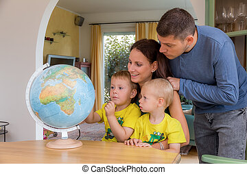family planning holiday travel - a family sitting at a globe...