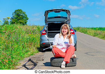 woman sitting on the spare wheel with the tools on the road
