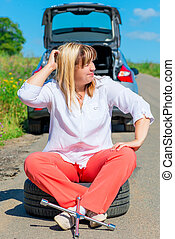 mature female driver sitting in the spare wheel on a sunny...
