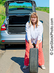 mature woman posing with a spare wheel near the car