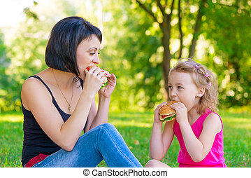 Mother and daughter eating sandwiches at a picnic in the park