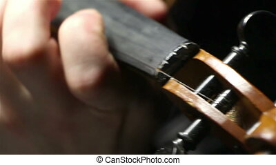 Playing chords on a broken violin, video on black background