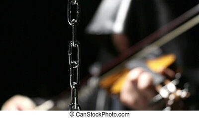 Chain and man playing on a fiddle, video on black background