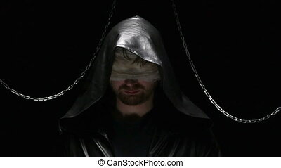Blind man taking off a hood, video on black background