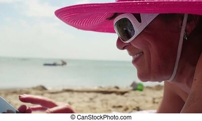 middle aged woman in hat and sunglasses uses mobile phone on...