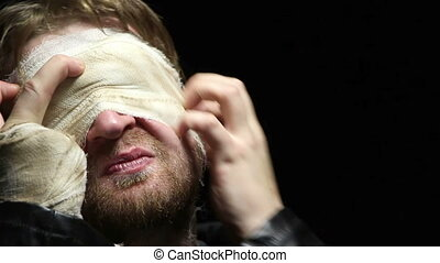 Blind blond man taking off a bandage, video on black...