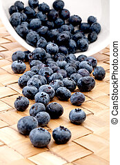 blueberries spilling from a bowl onto a placemat