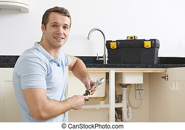Portrait Of Plumber Fixing Sink