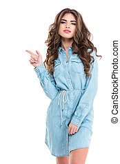 Beautiful young woman with long curly hair pointing away -...