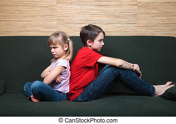 Siblings sulking after fight - Brother and sister wearing...