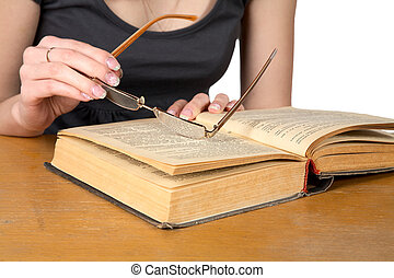 Hands of  girl with glasses over the opened book isolated