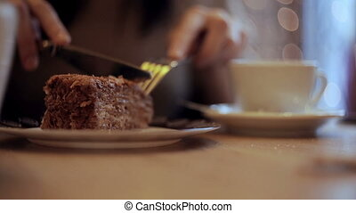 Girl eating cake and drinking coffee in cafe