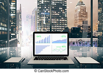 Business chart on laptop screen on glassy table in the office with night city view