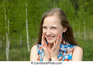 girl with a smile against young birches in the spring