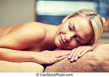 young woman lying on massage table in spa