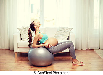 happy pregnant woman exercising on fitball at home -...