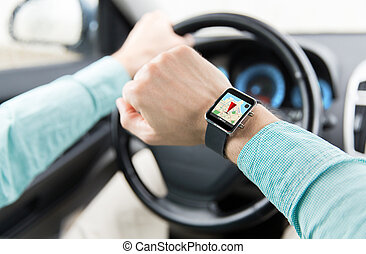 close up of man driving car with gps on smartwatch -...