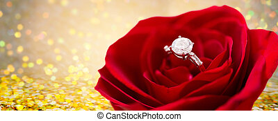 close up of diamond engagement ring in rose flower -...