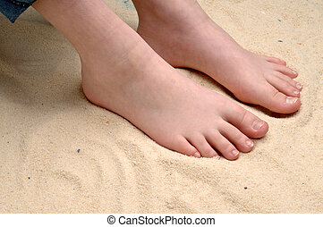 horizontal image of a childs feet in the sand