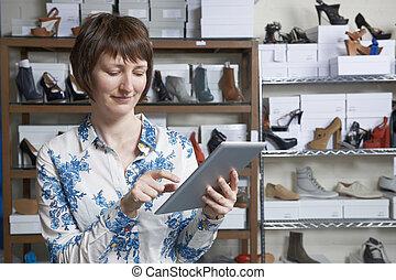 Owner Of Online Shoe Business Using Digital Tablet