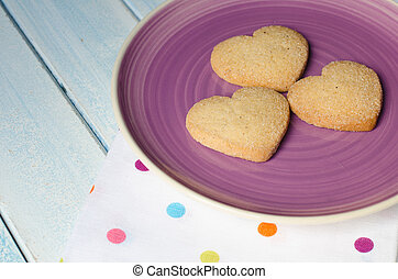 Heart-shaped butter cookies with sugar. - Purple plate with...