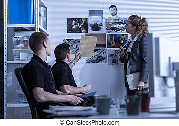 Police officers searching files - Horizontal view of police...