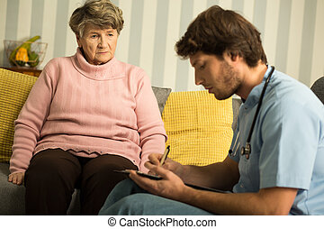 Doctor during private home visit - Image of doctor during...