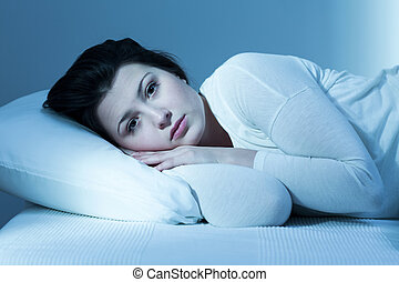 Woman and lack of sleep - Troubled young woman in bed and...