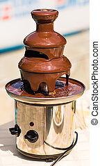 Chocolate fountain placed on a table in wedding day.