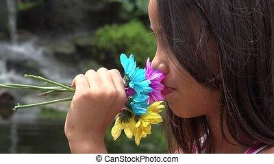 Hispanic Girl Smelling Flowers