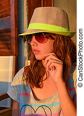 Preteen girl with hat and sunglasses in sunset light