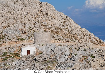 Chapel in the hills, Halki - A small chapel and an old stone...