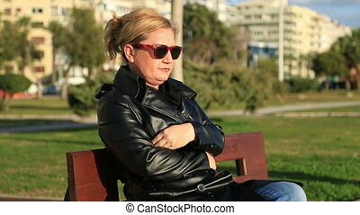 Sad woman sitting on the park bench - Portrait of a...