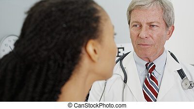 Senior doctor talking to adult woman in the office