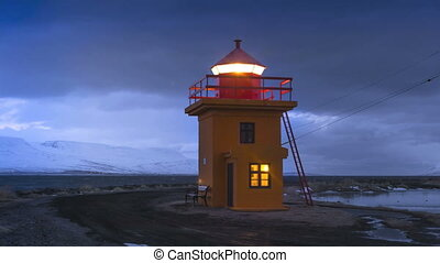 Time lapse of orange lighthouse at night in Iceland