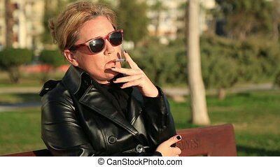 Sad woman sitting on a park bench and smoking cigarette