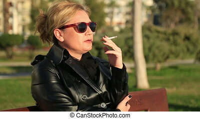 Woman smoking cigarette - Sad woman sitting on a park bench...