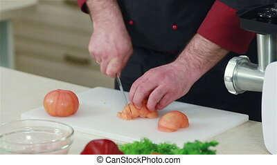 Hands cutting up peeled tomatoes - Close-up of chef cutting...