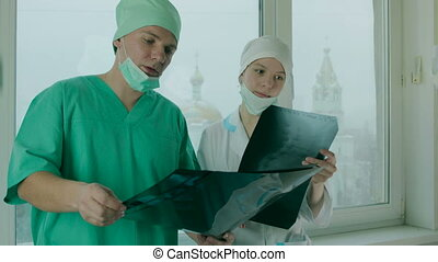 Two Doctors Watching X-Ray Pictures - Medium shot of two...