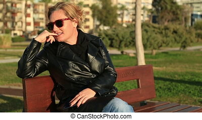 Woman using smart phone - Woman sitting on a park bench and...