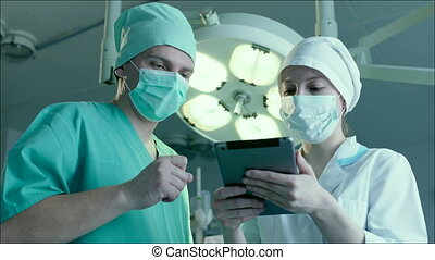 Nurse Writing Down Directions of a Doctor - Surgeon is...
