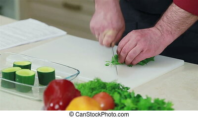 Close-up of a chef hands chopping parsley