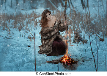 Girl shaman is heated by fire in winter forest. - Girl...
