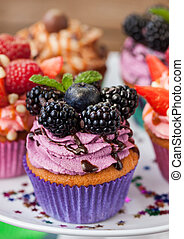 Delicious cupcake decorated with blueberry and blackberries
